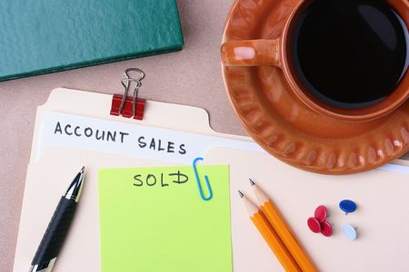 A manila account sales folder laying next to a cup of coffee and office supplies. Stock Photo - 7845082