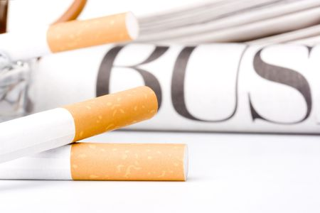 Filtered cigarettes laying in front of a newspaper and an ashtray. Stock Photo