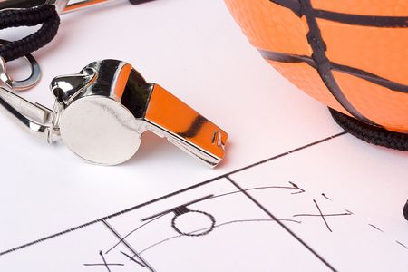 whistle: A silver whistle laying next to an orange basketball and the drawing of a game plan.