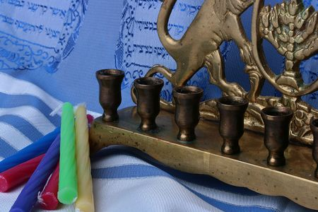 simchat torah: Jewish menorah and colorful candles laying on a blue and white tallit.