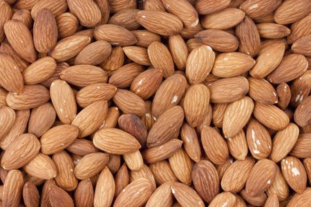Nuts Almond are scattered as a background on a table.