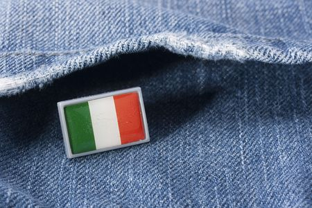 Flag of Italy against a pocket of dark blue jeans trousers.