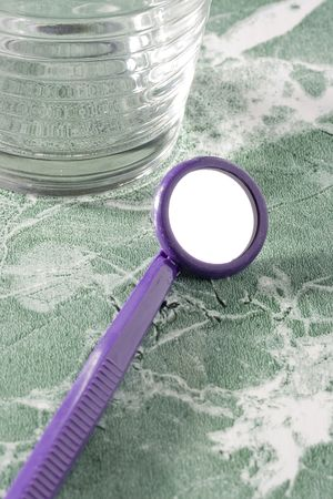 Purple dental mirror on the green countertop. Stock Photo - 7845347