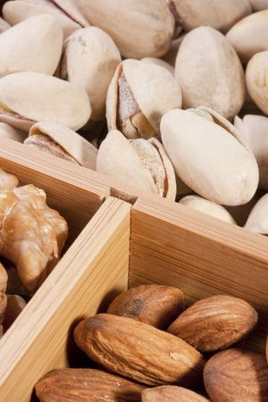 Nuts Almond in a wooden box together with nuts of other grades.