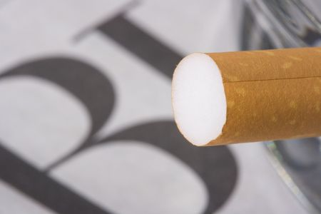 A cigarette filter in front of a newspaper with the word business on it.