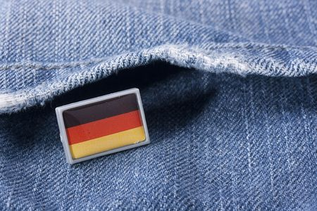 Flag of Germany against a pocket of dark blue jeans trousers.