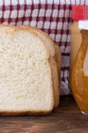 Yellow jam in bank and a white bread for a sweet sandwich.