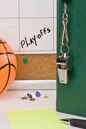 A silver whistle on a green notebook next to an orange basketball and a calendar with the date of the playoffs on it. Banco de Imagens