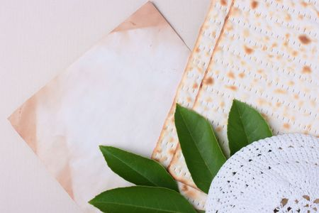 A white kippah and matzah laying next to an old piece of paper. Add your text to the paper. photo