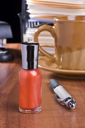 一杯のコーヒーの前にオフィスのテーブルの上にオレンジのマニキュア立って。 写真素材
