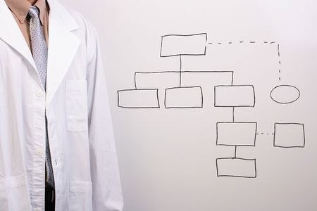 oncologist: Man in a shirt, tie, and a white lab coat standing next to a drawing of a plan.