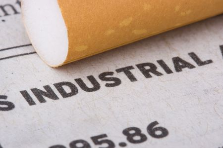 A filtered cigarette laying on a newspaper next to the word industrial. Stock Photo
