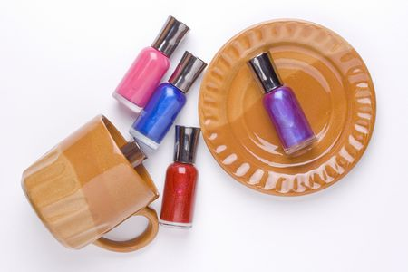 nail polish bottle: Nail polish placed on a brown plate and near a brown cup.