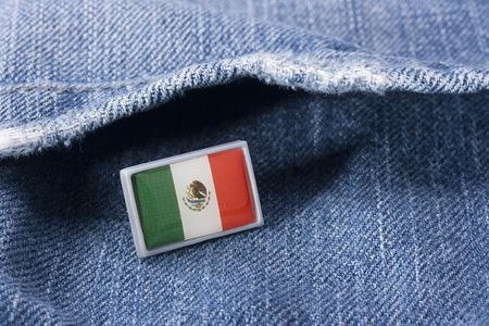 Flag of Mexico against a pocket of dark blue jeans trousers.