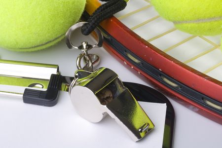 A silver whistle laying next to a tennis racquet and tennis balls. photo