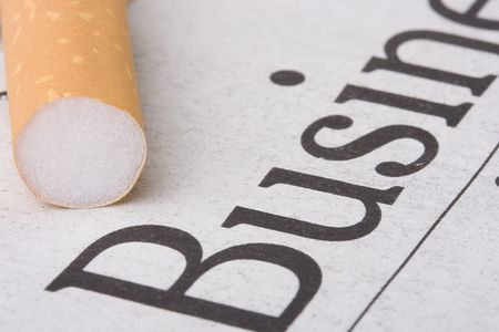 A filtered cigarette laying on a newspaper with the word business on it.