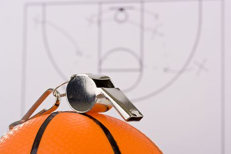 A silver whistle laying on an orange basketball in front of the game plan. photo