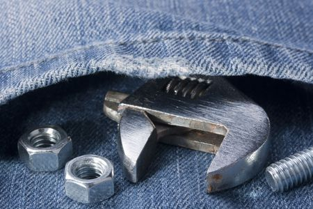 Wrench with bolts and nuts against a pocket of jeans. Stock fotó