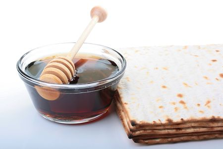 Honey in glasswares with wooden honey dipper and matsa. photo