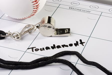 A silver whistle laying next to a white baseball on a calendar. photo