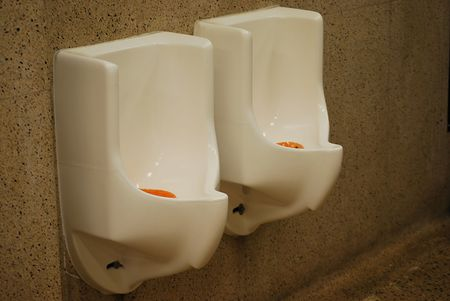 latrine: Urinals in a public men is room.