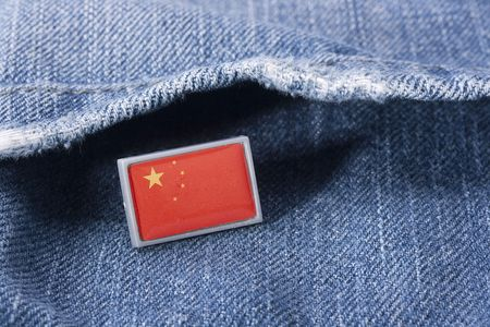 Flag of China against a pocket of dark blue jeans trousers. Stock fotó