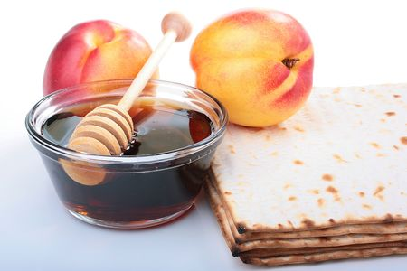 Honey in a glass vase with a special spoon, matzah and nectarine. Imagens
