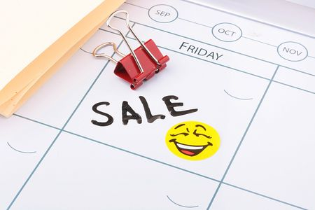 Word sale written on a calendar next to a smiley and a paper clip. Stock Photo - 8006999