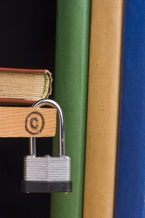 lock symbol: Copyright symbol on a piece of wood attached to a lock by a couple of books.