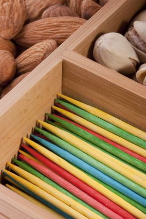Wooden multi-coloured toothpicks for personal hygiene. Nuts as a background. Imagens