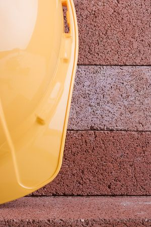 Yellow hard hat on a background of red bricks. photo