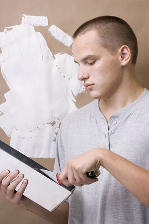 Caucasian man plastering a brown wall with white plaster.