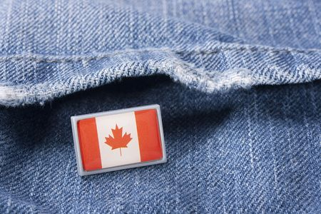 Flag of Canada against a pocket of dark blue jeans trousers.