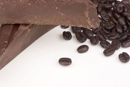 endorphines: Bitter chocolate in pieces with coffee grains on a white background.