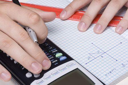 trigonometry: Student solving a trigonometry problem using a calculator. Stock Photo
