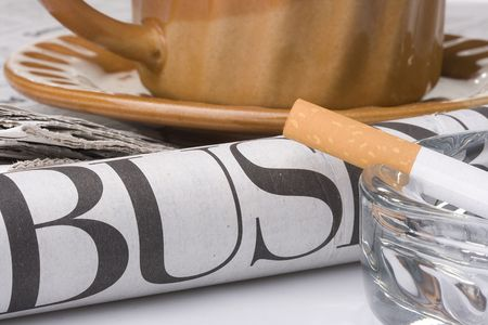 A filtered cigarette resting on a glass ashtray next to a brown cup and plate and a newspaper. photo