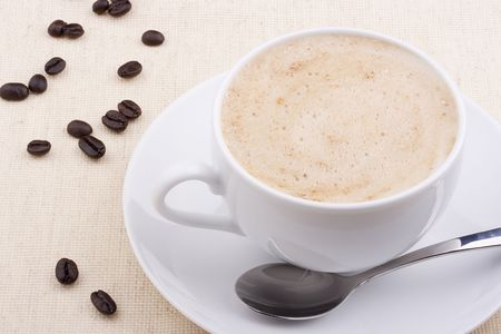 Cappuccino in a white ceramic cup with coffee grains. photo
