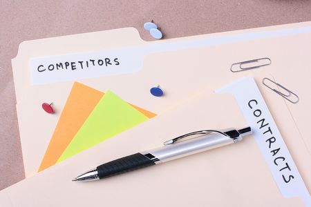 Manila competitors and contracts folders laying next to business supplies. Stock Photo - 8075419