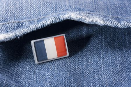 Flag of France against a pocket of dark blue jeans trousers.