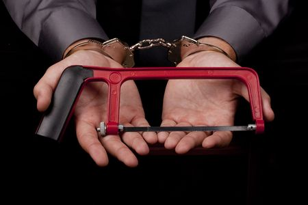 sequestration: Arrested in handcuffs holding a hacksaw with a goal to remove the handcuffs. Stock Photo