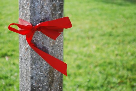 Concrete pole tied with red ribbon, green natural background.