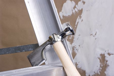 Drywall hammer on a step ladder next to a brown drywall.