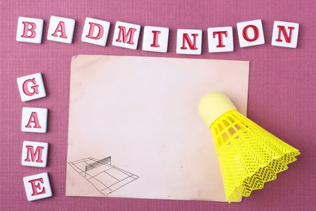 A yellow synthetic badminton shuttlecock on a piece of paper. Add your text to the paper. photo