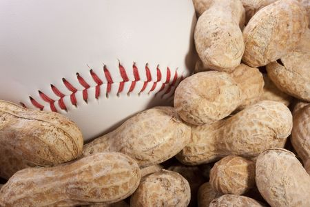 Nuts Peanuts on a table together with a baseball ball.