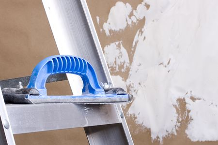 plastering: Plastering trowel laying on a step ladder next to a brown wall with plaster on it. Stock Photo