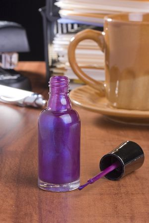 nail polish bottle: Open purple nail polish standing on a table in front of a cup of coffee.