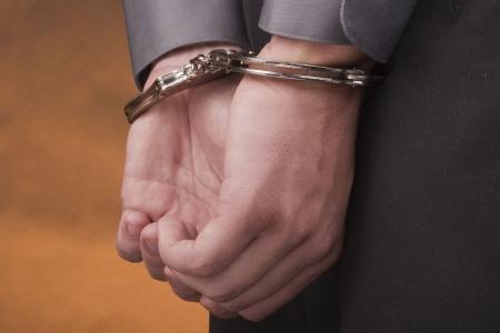 manacles: Arrest� a sus manos esposados detr�s de su espalda.