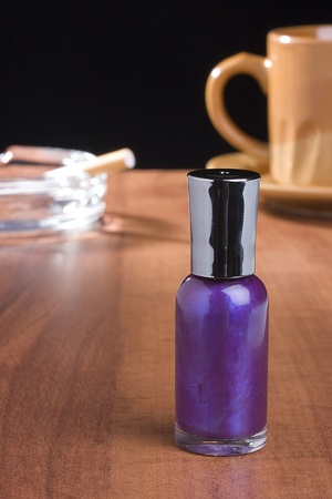 A bottle of purple nail polish standing on a coffee table in front of a cup of coffee and an ashtray. Фото со стока
