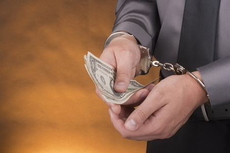 confiscation: Arrest, close-up mans hands with money in handcuffs. Stock Photo