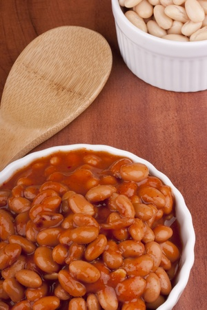 White canned beans in a white ceramic dish with red sauce. photo